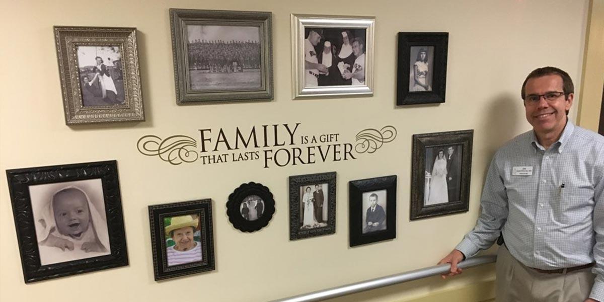 administrator joe bohunicky stands near the new photo wall at mount carmel rehabilitation and nursing center