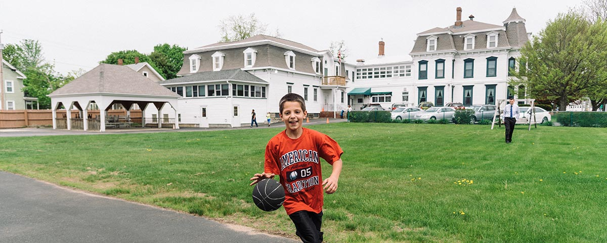 A child dribbles a basketball in the playground at the St. Charles School in Rochester, NH. St. Charles School program requirements image.
