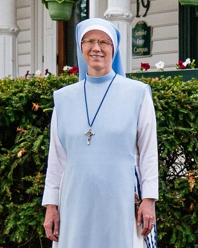sr. mary agnes Dombroski stands in front of the st charles school