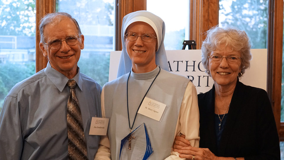 Sr. Mary Agnes Dombroski, recipient of the In His Footsteps Award, flanked by her parents Jim and Jane.