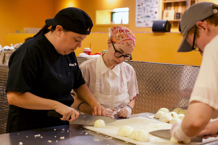 NH Food Bank Recipe for Success Production Assistant Moriah Webster trains students.